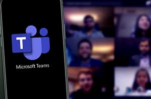 Microsoft Teams Logo on Phone and Microsoft Teams Meeting on Computer in Background